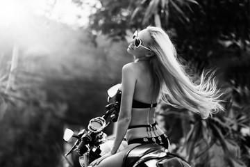 Fashion model biker girl on a motorcycle. Black & white photo