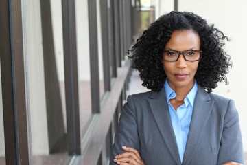 Portrait in full growth. Very confident, powerful and aggressive Businesswoman wearing glasses crossing her arms with copy space