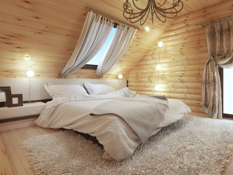 Bedroom interior in a log on the attic floor with a roof window.