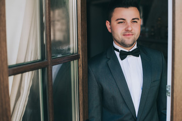 Sexy fashionable man celebrity in tuxedo indoor