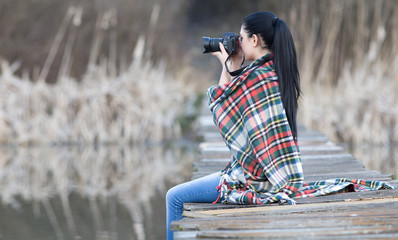Girl shooting with photo camera on the river