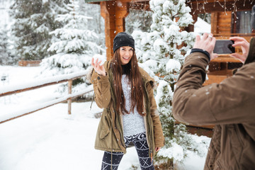 Woman posing to boyfriend taking pictures with smartphone in winter