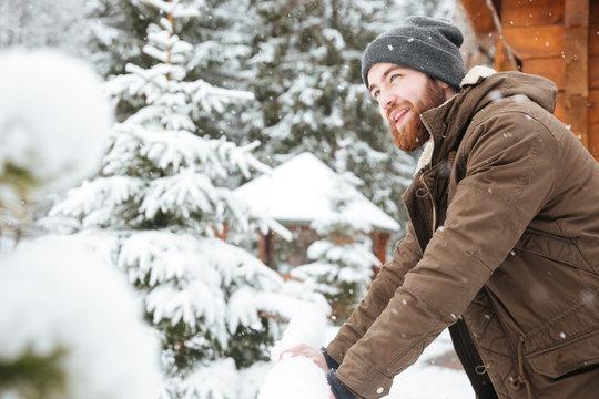 Happy man standing and enjoying snowy weather on winter resort