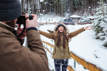 Male photographer taking pictures of happy woman in winter forest
