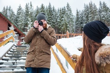 Smiling photographer taking photos of woman on stairs in winter