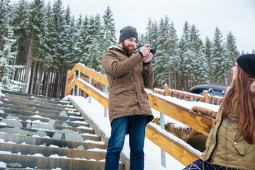 Male photographer taking pictures of woman on stairs in winter