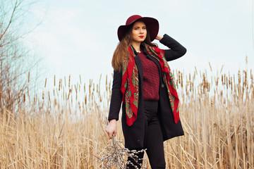 Молодая стильная девушка в пальто и шляпе