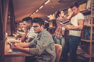 Multinational group of cheerful students studying in the university library.