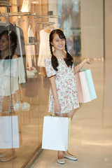 Beautiful young Vietnamese girl with many shopping bags