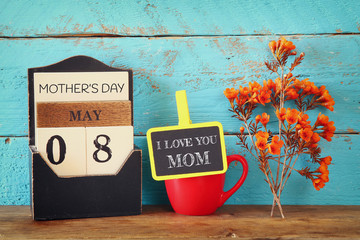 flowers next to blackboard on wooden table. happy mother's day concept