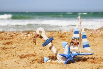 starfish, sailboat on sea sand and ocean horizon