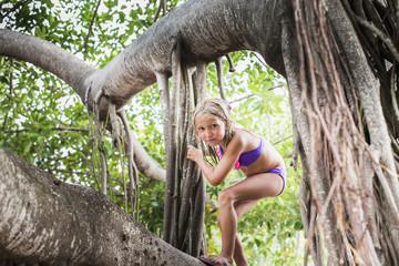 Caucasian girl climbing tropical tree