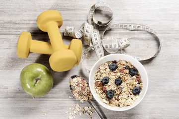 healthy lifestyle concept with exercise weight, muesli, tape and green apple