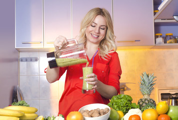 Happy young woman pouring freshly made smoothie in the glass