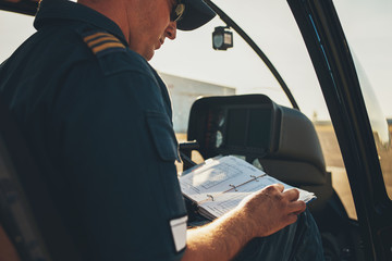 Man helicopter pilot reading a manual booklet