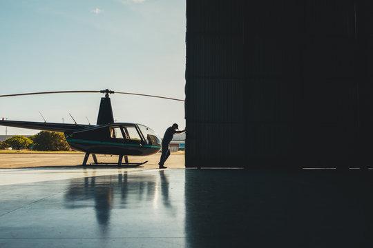 Pilot opening the helicopter hangar door.