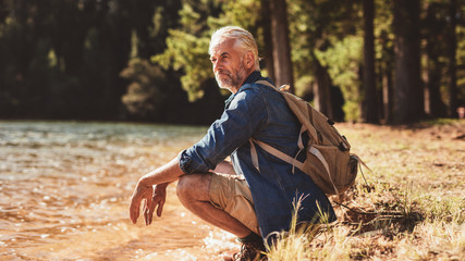 Senior male hiker relaxing by a lake and admiring the view Wall mural