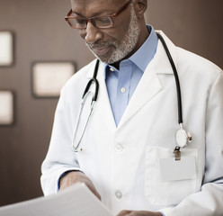 Black doctor reading charts in office