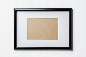 Black plain empty thin wood picture frame with white mat passe-partout on white bricks background