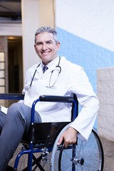 Happy male doctor sitting on wheel chair