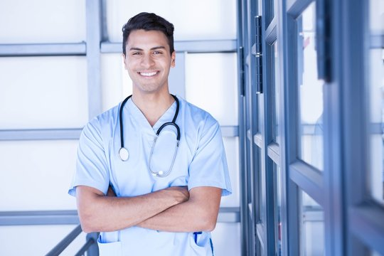 Happy male doctor standing with arms crossed