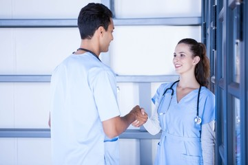 Doctors shaking hands in corridor