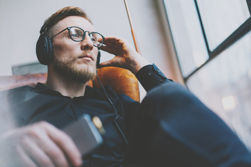 Portrait handsome bearded man glasses,headphones listening to music modern loft studio.Man sitting in vintage chair,holding smartphone and relaxing.Panoramic windows background.Horizontal, film effect