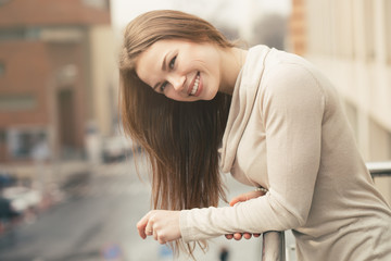 Beautiful young woman smiling in city