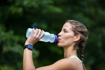 Marathon female athlete running drinking water