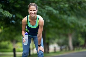 Marathon female athlete running drinking water