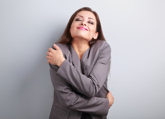 Happy business woman hugging herself with natural emotional enjo