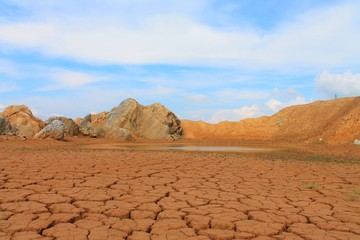 Cracked earth. Lake in the desert. Blue sky. The rocks and hills.