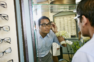 Filipino man trying on glasses at optometrist
