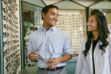 Man trying on glasses while standing with optometrist