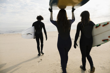 Surfers carrying boards on beach
