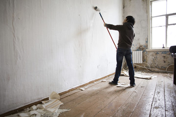 Mari man painting walls in new home