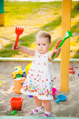 Little child playing with toys in sand on children playground. Infant girl standing in 