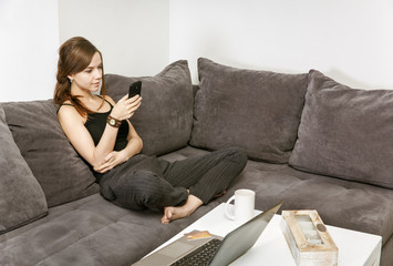 girl with mobile phone in hand sits on a sofa in cozy room