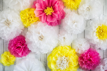 Paper handmade flowers isolated on white wood background. Beautiful floral background of white, pink and yellow colors.