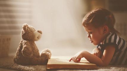 child little girl reading a magic book in dark home
