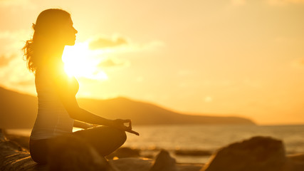 Wall Mural - woman meditating in lotus pose on beach at sunset