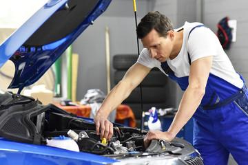 KFZ-Mechaniker repariert Fahrzeug in einer Werkstatt // car mechanic in garage