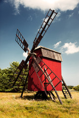 Red windmill, yellow field and blue sky on Baltic Sea island Oland, Sweden