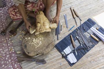 Craftsperson shaping wooden piece in studio