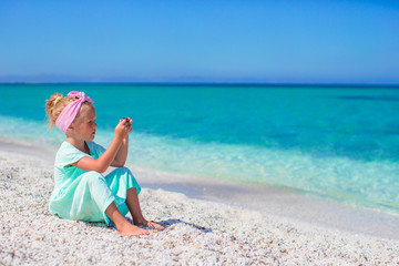Little adorable girl with phone during beach vacation
