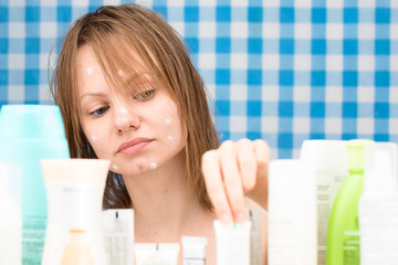 Girl is choosing a cosmetic product among set of cosmetics in ba