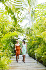 Lesbian couple holding hands on tropical walkway