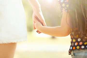 Mother's hand lead her child daughter outdoors, trust family concept