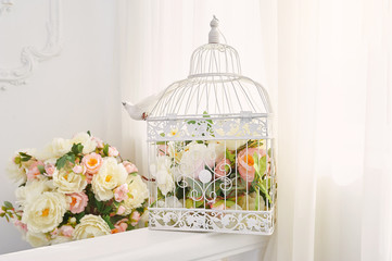 Decorative bird cage with bouquet of flowers in the interior