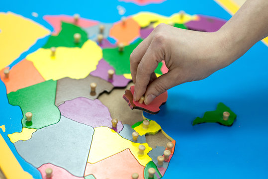 Child playing with wooden block map